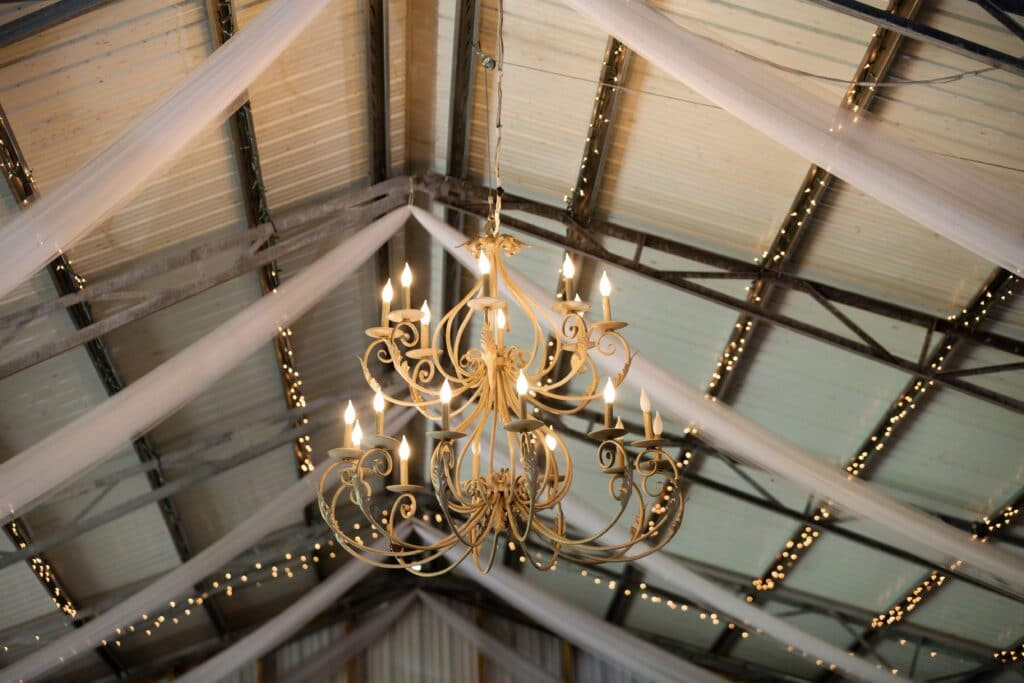 white ceiling with wood rafters and gold chandeliers